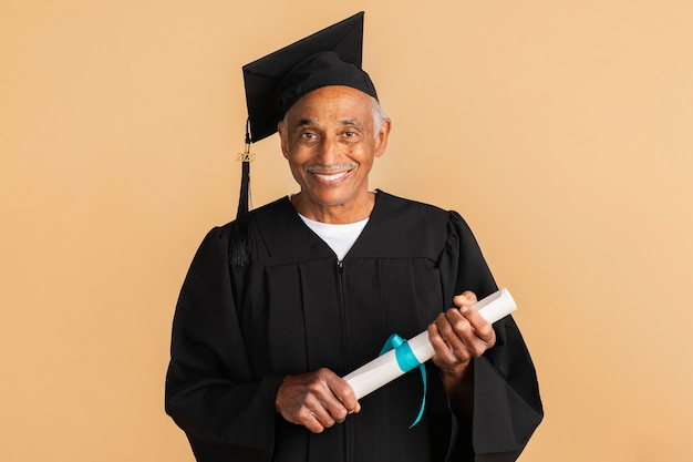 Dumny starszy mężczyzna w sukni ukończenia szkoły trzymający dyplom