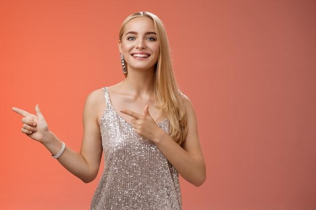 Dumny szczęśliwy przystojny stylowy blond atrakcyjna kaukaska kobieta w srebrnej luksusowej sukience glamour, wskazując w lewo uśmiechając się szeroko, pokazując przyjaciołom nowe mieszkanie, stojąc na czerwonym tle.