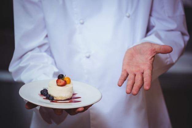 Dumny szef kuchni trzyma talerz sernik pustyni