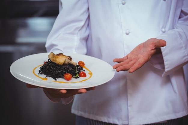 Dumny szef kuchni trzyma talerz spaghetti z atramentem kałamarnicy