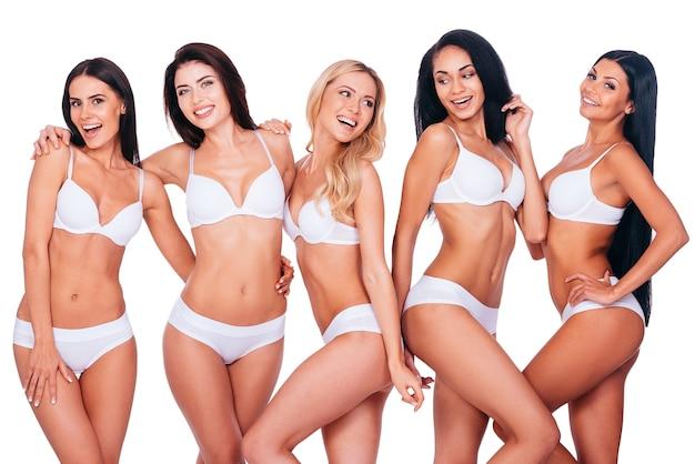 Dumny z bycia naturalnym. pięć pięknych młodych kobiet w bieliźnie, które łączą się ze sobą i uśmiechają, stojąc razem na białym tle