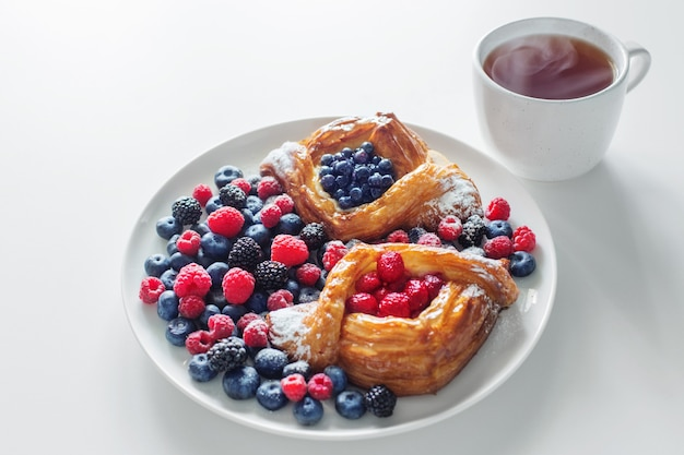 Duński z malinami i jagodami z filiżanką herbaty na białym stole