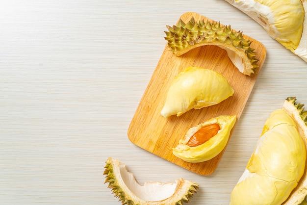 Durian dojrzały i świeży, skórka duriana na drewnianej desce