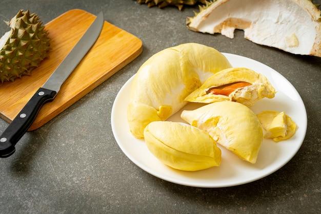 Durian dojrzały i świeży, skórka z duriana na białym talerzu