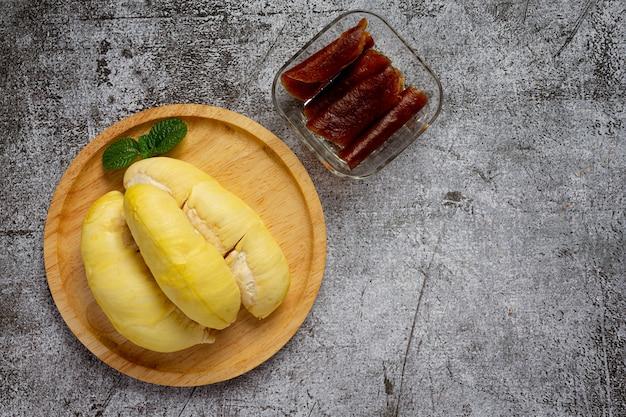 Durian i przekąski na ciemnej powierzchni.