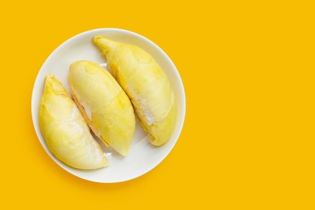 Durian w białej płytce na żółtym tle.