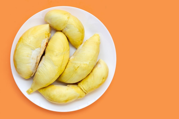 Durian w białym talerzu na pomarańczowym tle.