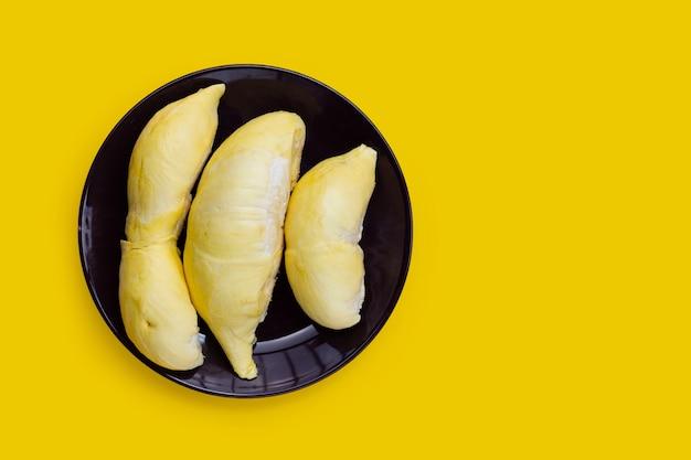 Durian w talerzu na żółtym tle.