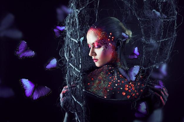 Dusza uwalnia się z klatki. młoda atrakcyjna dziewczyna w jasnym makijażu artystycznym, dużo motyli