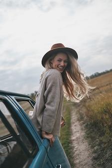 Dusza żądna przygód. atrakcyjna młoda uśmiechnięta kobieta wychylająca się przez okno furgonetki i patrząca w kamerę podczas podróży samochodem