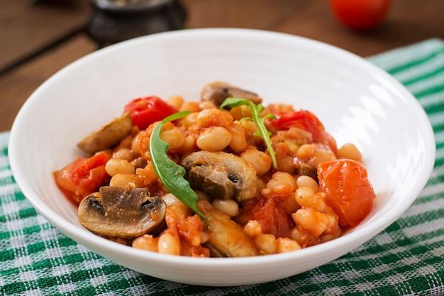 Duszona biała fasola z pieczarkami i pomidorami z pikantnym sosem w białej misce