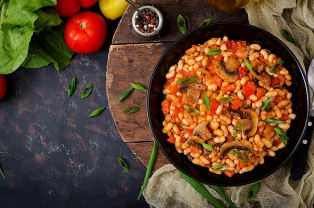 Duszona biała fasola z pieczarkami i pomidorami z pikantnym sosem w czarnej misce. . leżał płasko