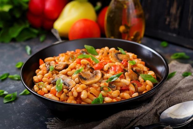 Duszona biała fasola z pieczarkami i pomidorami z pikantnym sosem w czarnej misce.