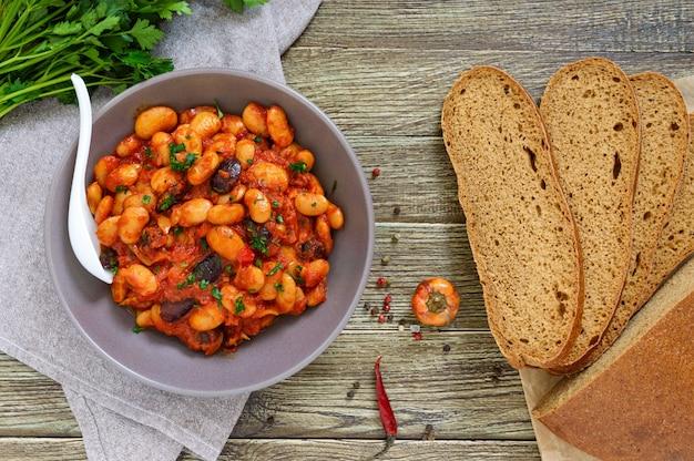 Duszona bób w sosie pomidorowym z bliska zioła i przyprawy, kromki chleba żytniego na drewnianym stole. wielkopostne menu. danie wegańskie widok z góry.