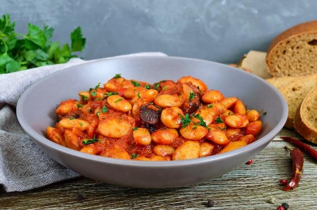 Duszona bób w sosie pomidorowym z bliska zioła i przyprawy, kromki chleba żytniego na drewnianym stole. wielkopostne menu. danie wegańskie