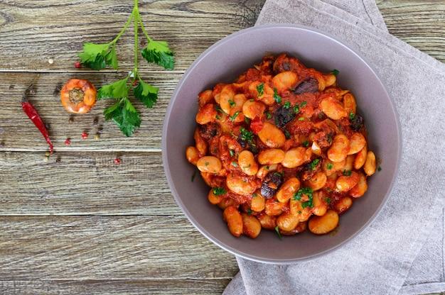 Duszona bób w sosie pomidorowym z bliska ziołami i przyprawami na drewnianym stole. widok z góry.