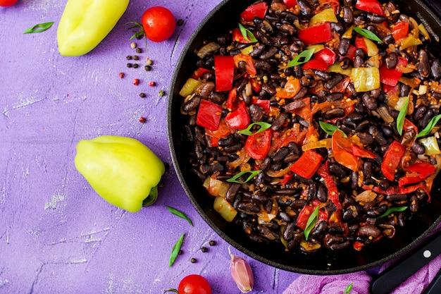 Duszona czarna fasola ze słodką papryką i pomidorami z pikantnym sosem na patelni. flay leżał. widok z góry