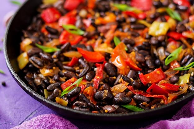 Duszona czarna fasola ze słodką papryką i pomidorami z pikantnym sosem na patelni.