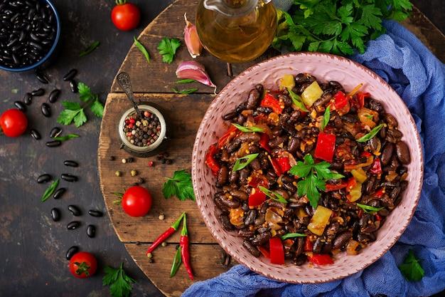 Duszona czarna fasola ze słodką papryką i pomidorami z pikantnym sosem w różowej misce