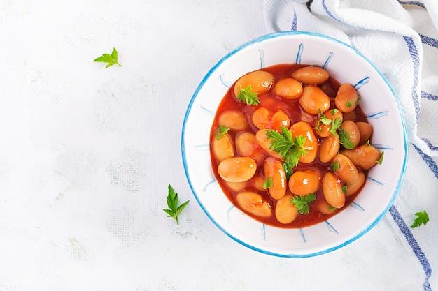 Duszona fasola w sosie pomidorowym z przyprawami. wegańskie jedzenie. widok z góry, płaski układ, miejsce na kopię