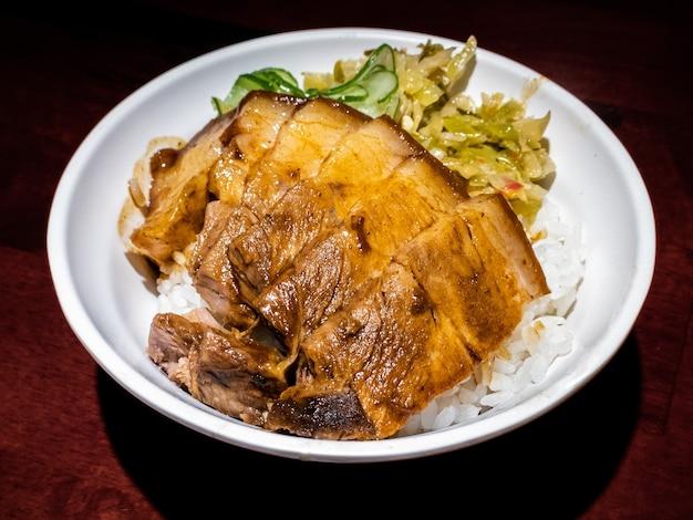 Duszona wieprzowina dongpo w brązowym sosie na białym ryżu, podawana na stole w restauracji. karmelizowany brzuch chińskiej świni. pyszne jedzenie, gotowanie tradycyjnej kuchni tajwańskiej. pyszne dania na kolację na tajwanie?