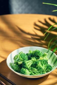 Duszone brokuły w sosie czosnkowym na białym talerzu. chińska receptura i kuchnia