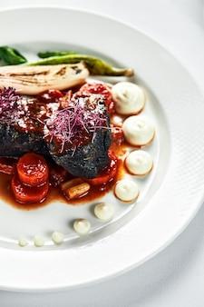Duszone policzki wołowe z warzywami, gotowane policzki wołowe w sosie z czerwonego wina ze smażonymi liśćmi szpinaku i marchewką na jasnym tle widok z góry