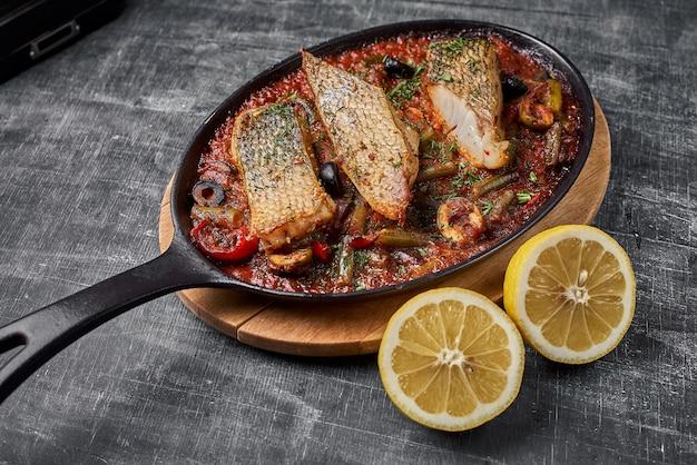 Duszony okoń w sosie pomidorowym, podawaj potrawy w stylu prowansalskim na patelni.