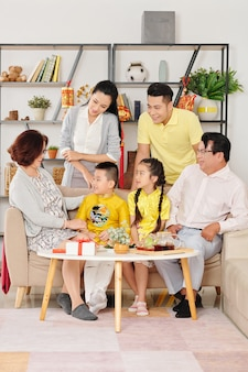 Duża azjatycka rodzina zebrała się, aby porozmawiać, napić się herbaty ze słodyczami i świętować chiński nowy rok