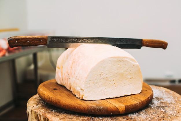 Duża biała serowa głowa na drewnianej desce z nożem. ser. tradycyjne produkty na rynku. ser rolnik na blacie w sklepie.