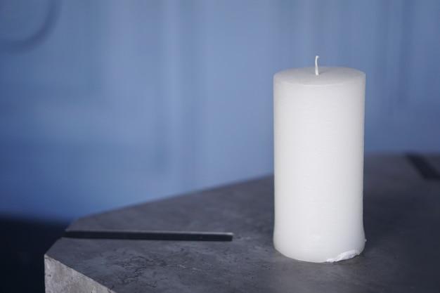 Duża biała świeca na niebieskim tle z miejscem na kopię