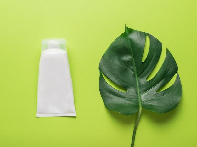 Duża biała tubka kremu i liść monstery na zielonym tle. koncepcja leczenia preparatami medycznymi wykonanymi z naturalnych składników. leżał płasko.