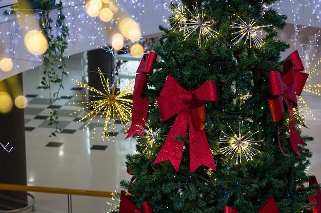 Duża choinka z czerwonymi kokardkami i światełkami w centrum handlowym zimowa dekoracja świąteczna