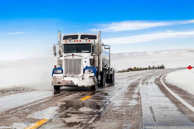 Duża ciężarówka jeździ po zaśnieżonej drodze