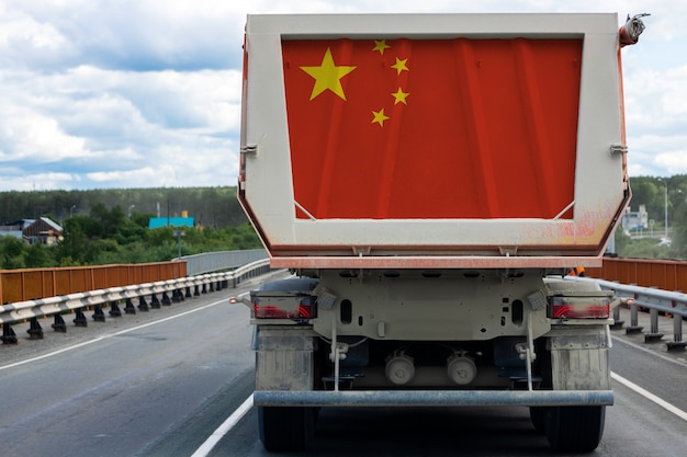 Duża ciężarówka z flagą narodową chin poruszająca się po autostradzie
