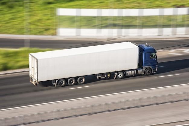Duża ciężarówka z przyczepą na autostradzie z prędkością poruszającą się po asfalcie, widok z góry.