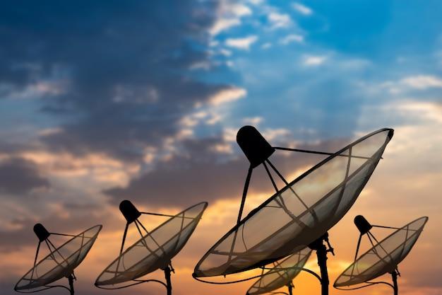 Duża czarna antena satelitarna na tle pięknego spiralnego nieba słońca, transmisja danych. tło nieba technologii cyfrowej.