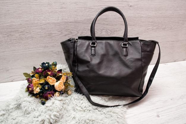 Duża czarna torebka damska na drewnianym, bukiet kwiatów i szare sztuczne futro.