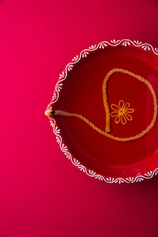 Duża czerwona dekoracyjna gliniana diya lub lampa naftowa zapalona podczas festiwalu diwali. selektywne skupienie