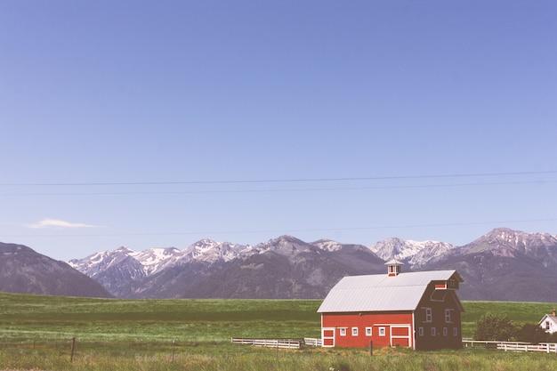 Duża czerwona drewniana stajnia w zielonym polu z skalistymi górami