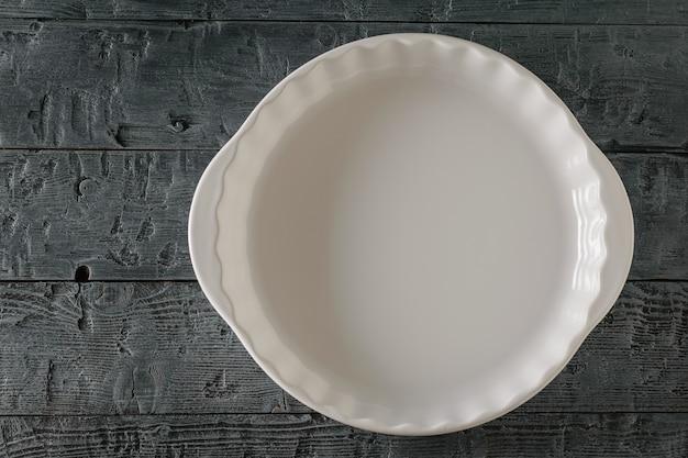 Duża drewniana miska na ciemnym drewnianym stole