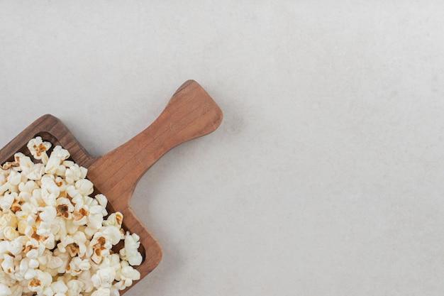 Duża drewniana taca z rączką zaopatrzona w porcję popcornu na marmurowym stole.