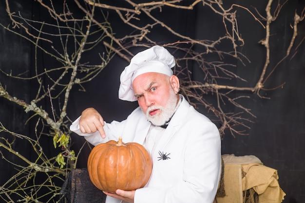 Duża dynia na halloween brodaty szef kuchni z dietą dyniową szef kuchni mężczyzna w białym fartuchu prezentującym