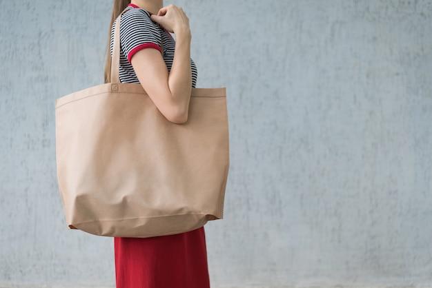 Duża ekologiczna torba na zakupy na ramieniu młodej kobiety. przestrzeń projektowa