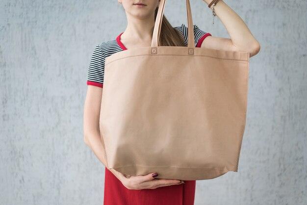 Duża ekologiczna torba na zakupy w rękach młodej kobiety. przestrzeń projektowa
