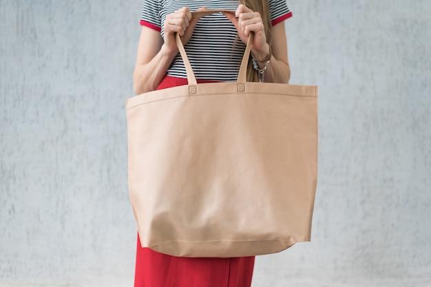 Duża ekologiczna torba na zakupy w rękach młodej kobiety.