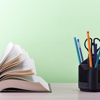 Duża, gruba książka ze stronami rozłożonymi jak wachlarz i stojak z długopisami, ołówkami i nożyczkami na stole na zielonym tle.