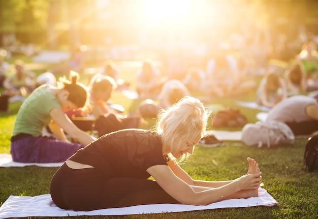 Duża grupa dorosłych na zajęciach jogi w parku