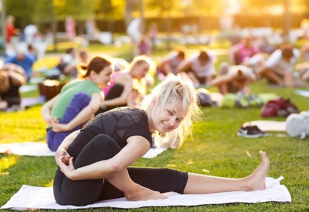 Duża grupa dorosłych uczestniczących w zajęciach jogi na świeżym powietrzu w parku