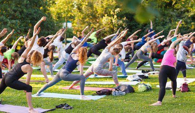 Duża grupa dorosłych uczęszczających na zajęcia jogi na świeżym powietrzu w parku